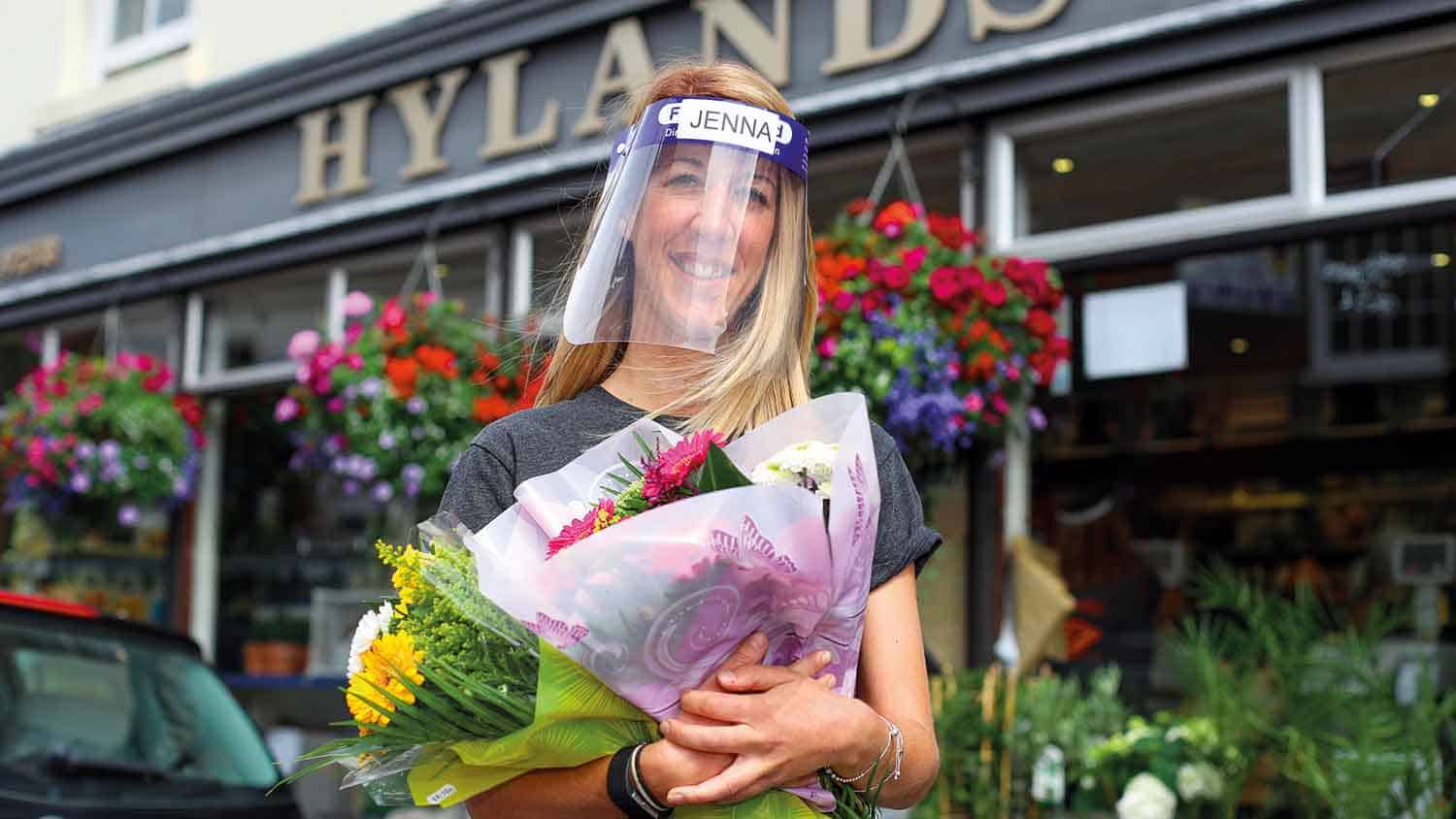 Florist outside her shop, carrying flowers, wearing PPE plastic face mask