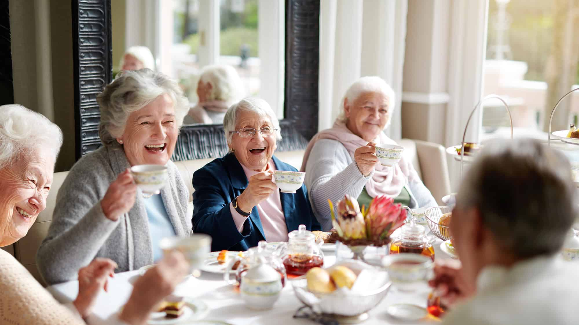 A group of older women enjoying a tea party