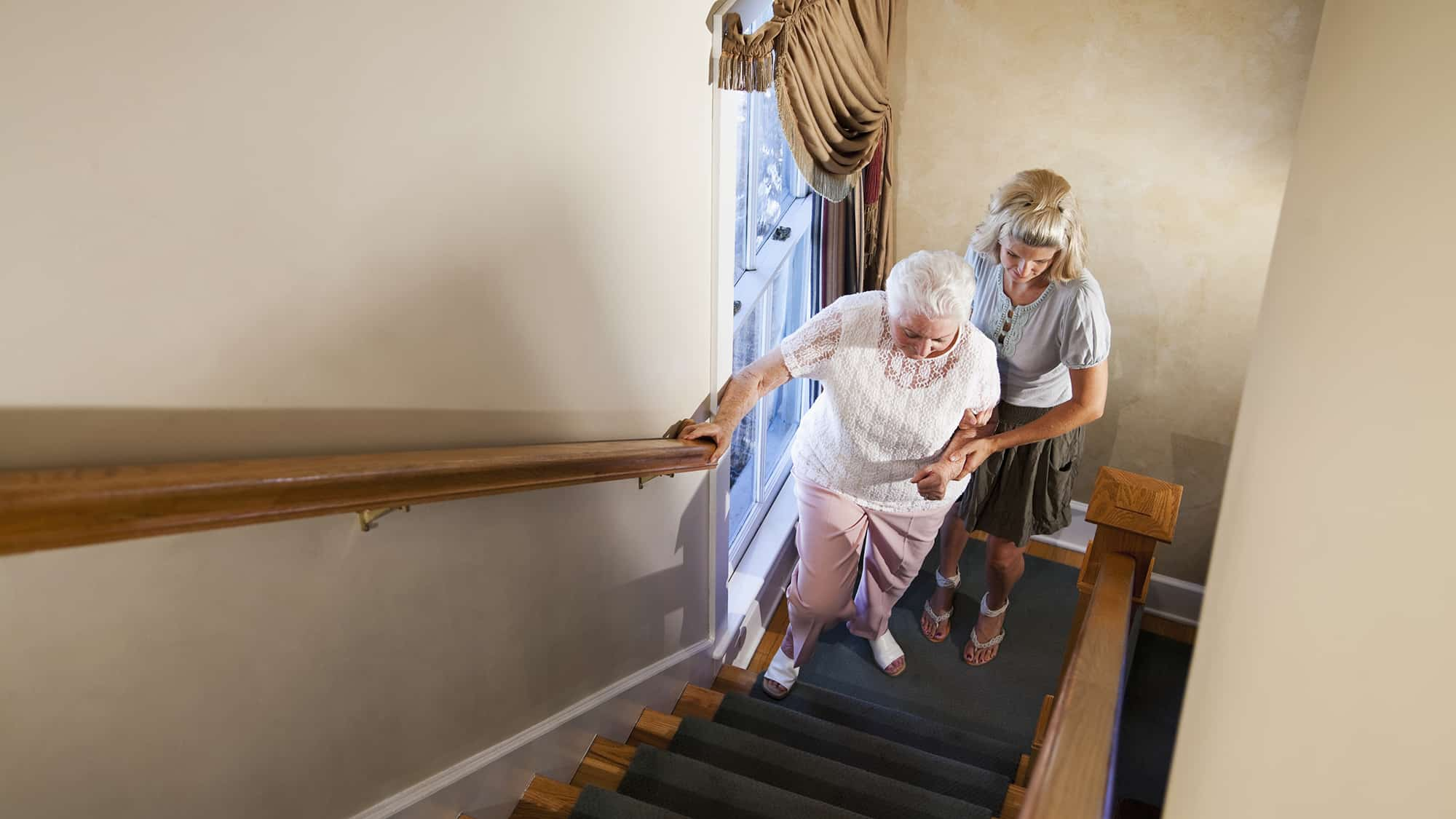 Woman helping a grandmother climb the stairs