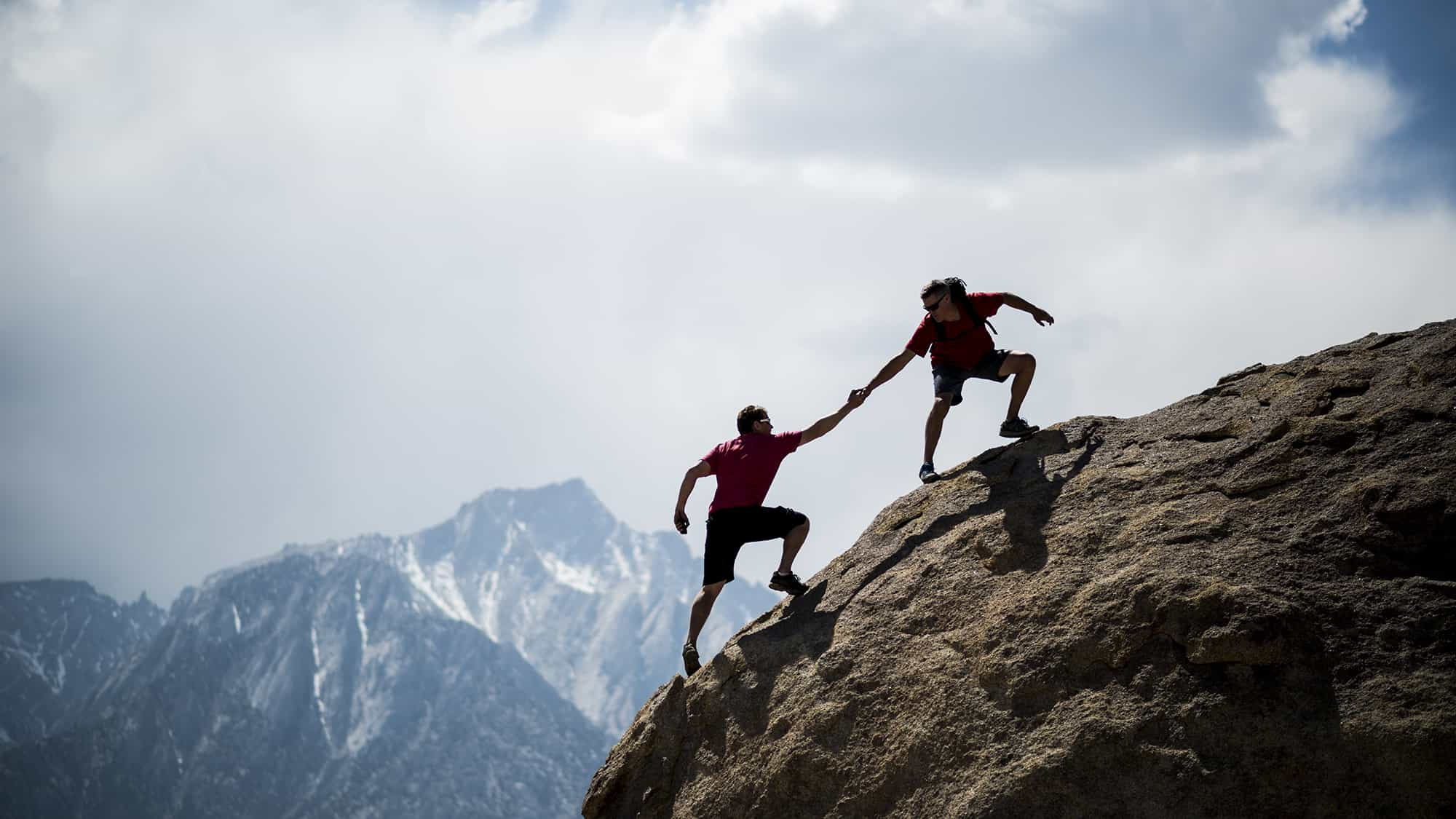 One climber helping another to the summit of a giant boulder