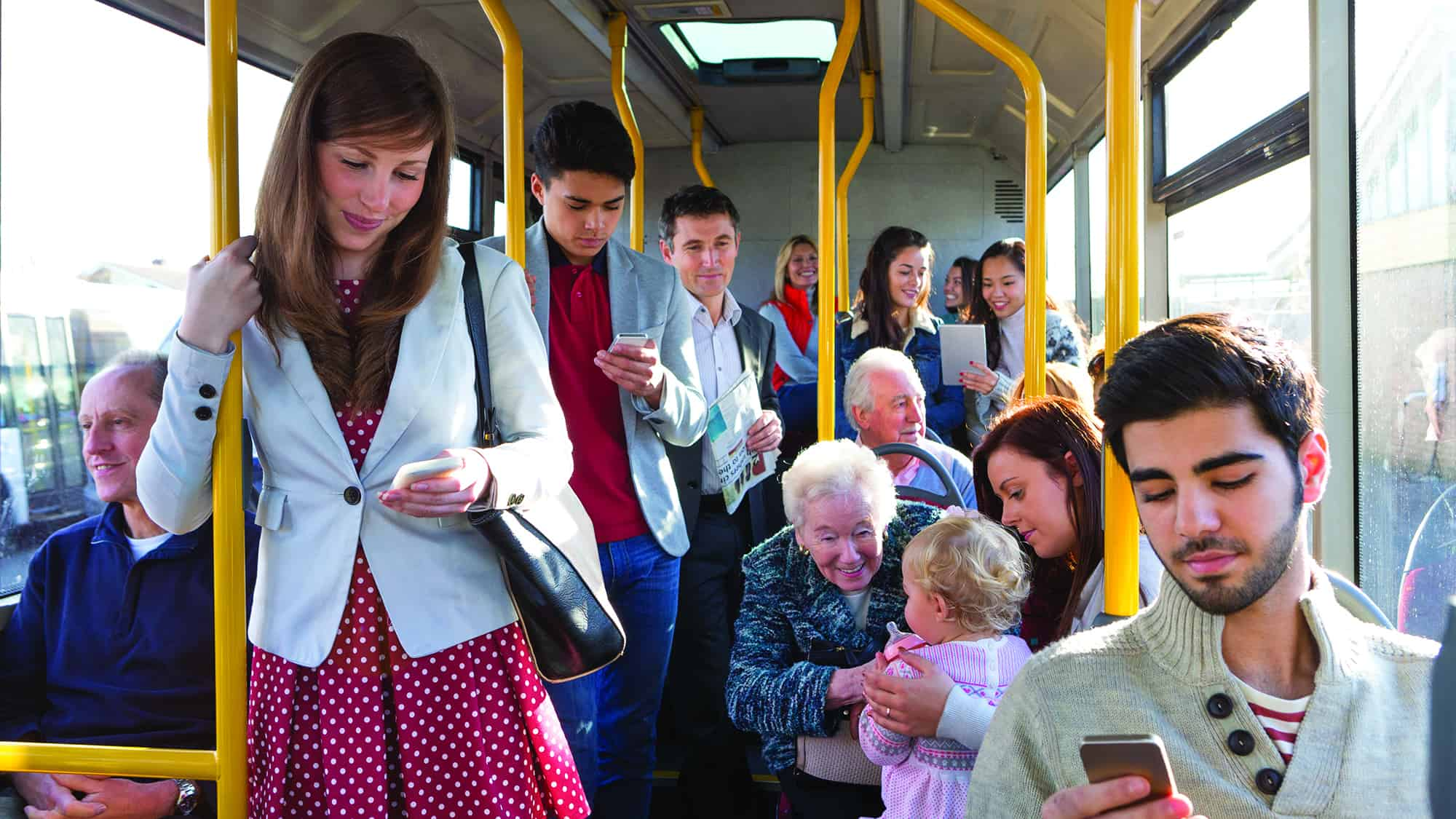 Mixed group of pedestrians using technology on the bus