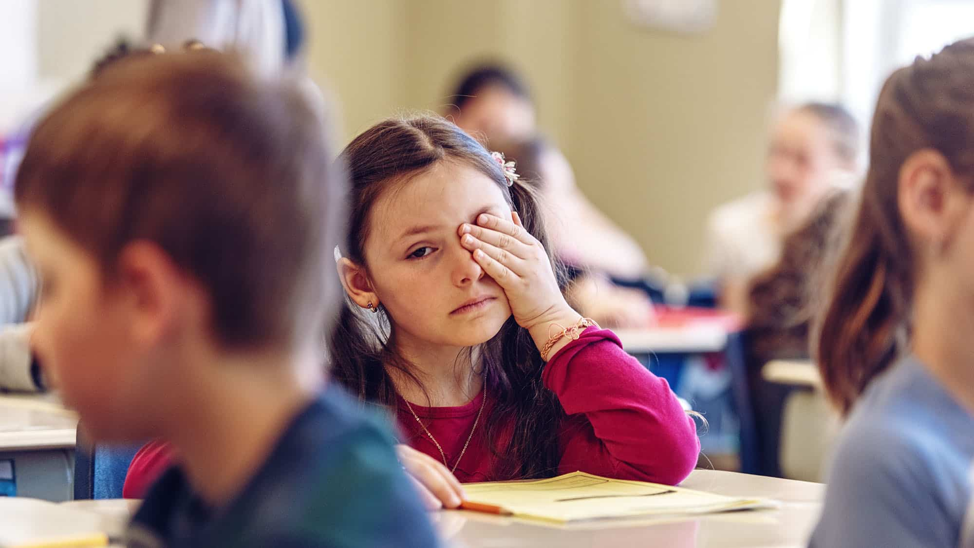 Sad schoolgirl in a classroom