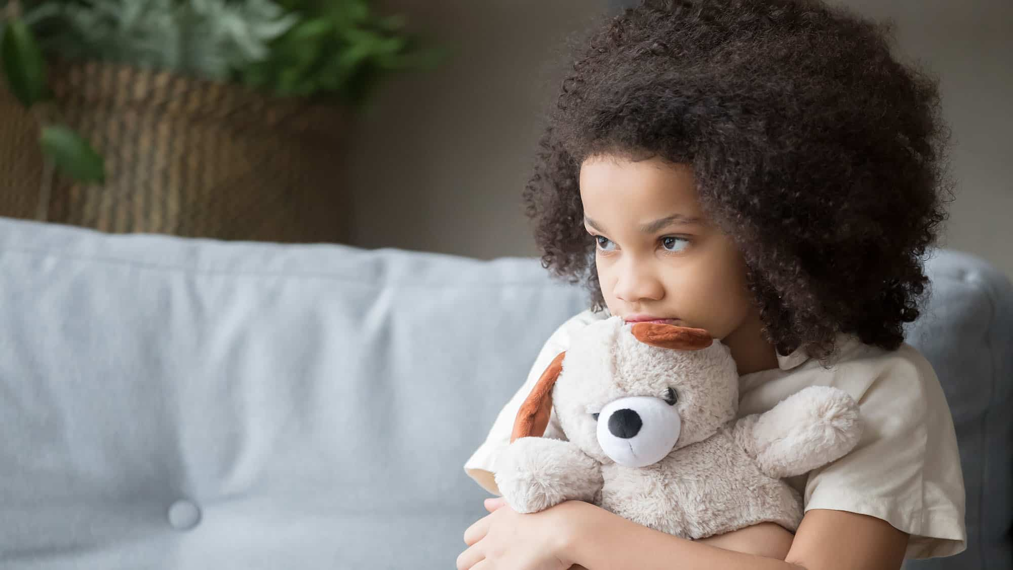 Upset lonely girl holding teddy bear looking away
