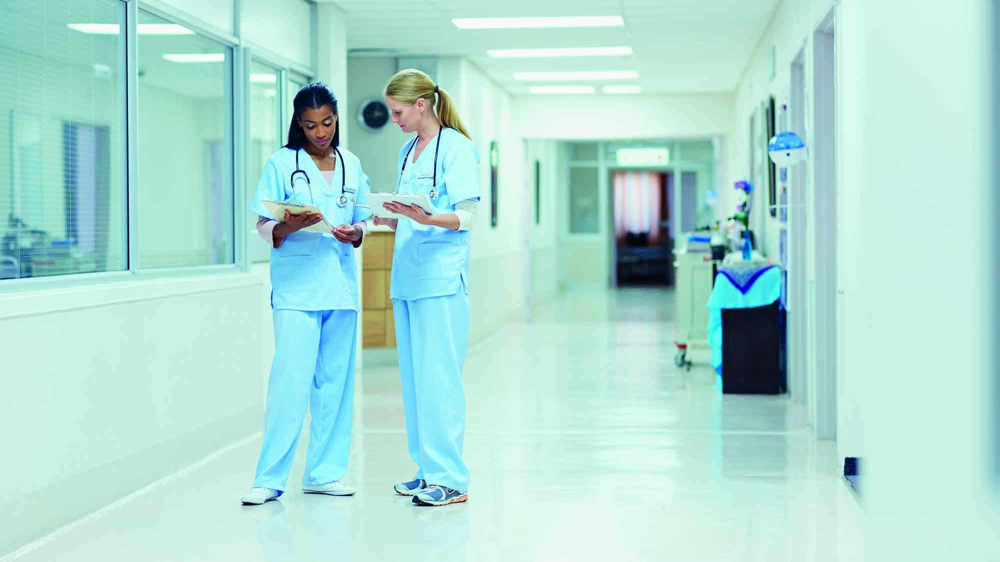 Nurses discussing medical documents in hospital