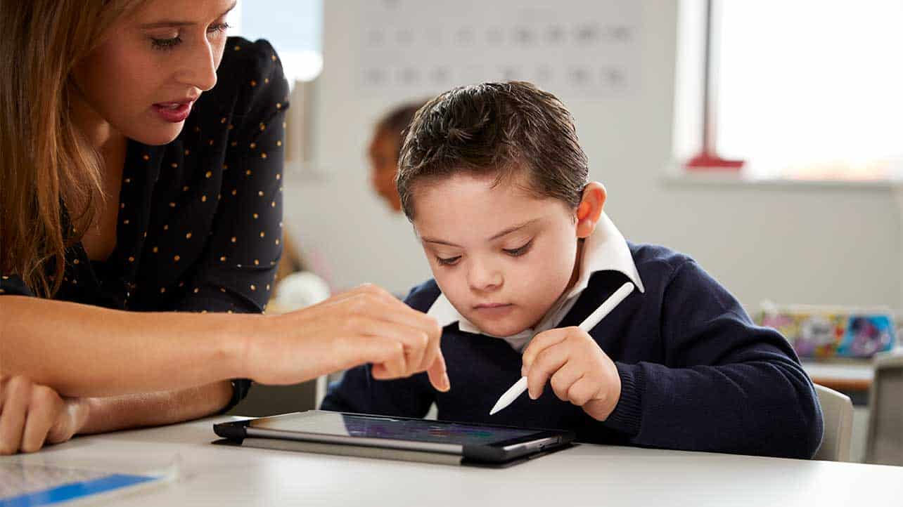 Child and a teacher using a tablet
