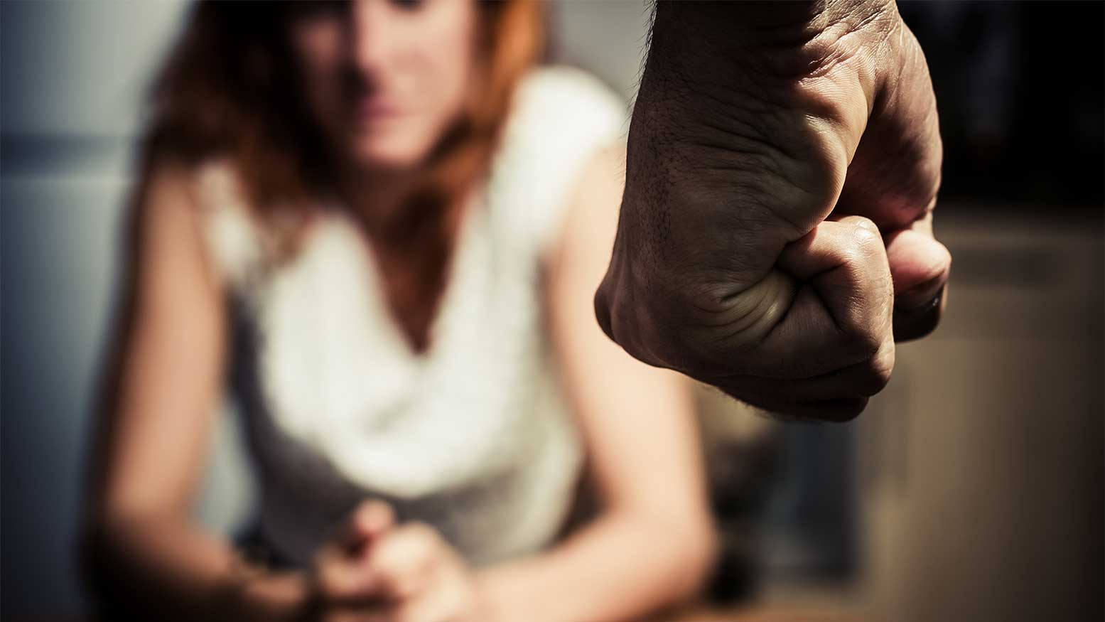 A clenched fist with a blurred woman in the background