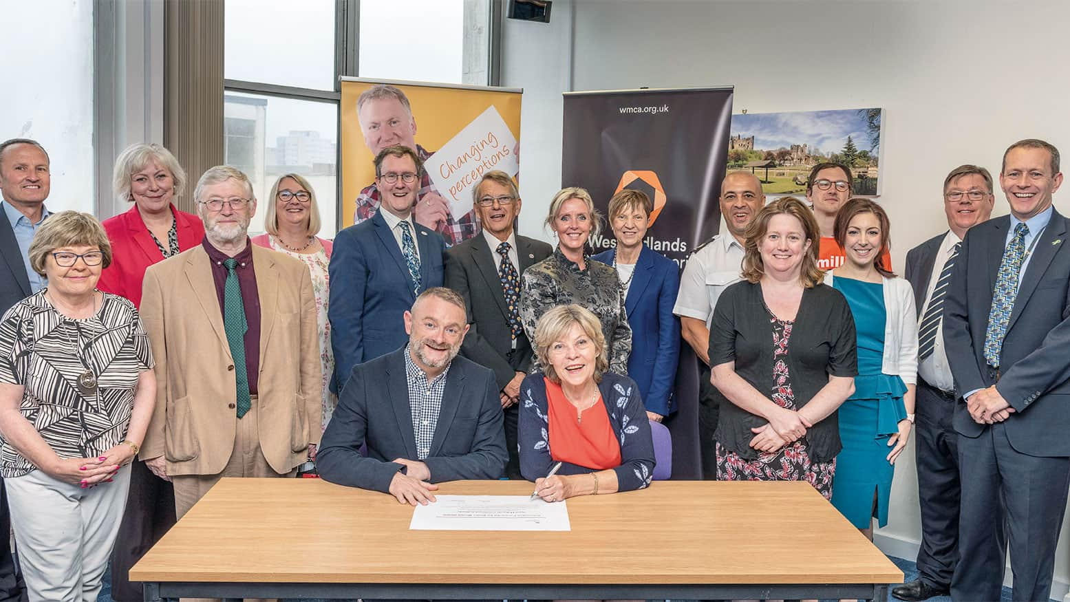 West Midlands Combined Authority's Wellbeing Board with (front) board Chair Cllr Izzi Seccombe signing the Prevention Concordat for Better Mental Health