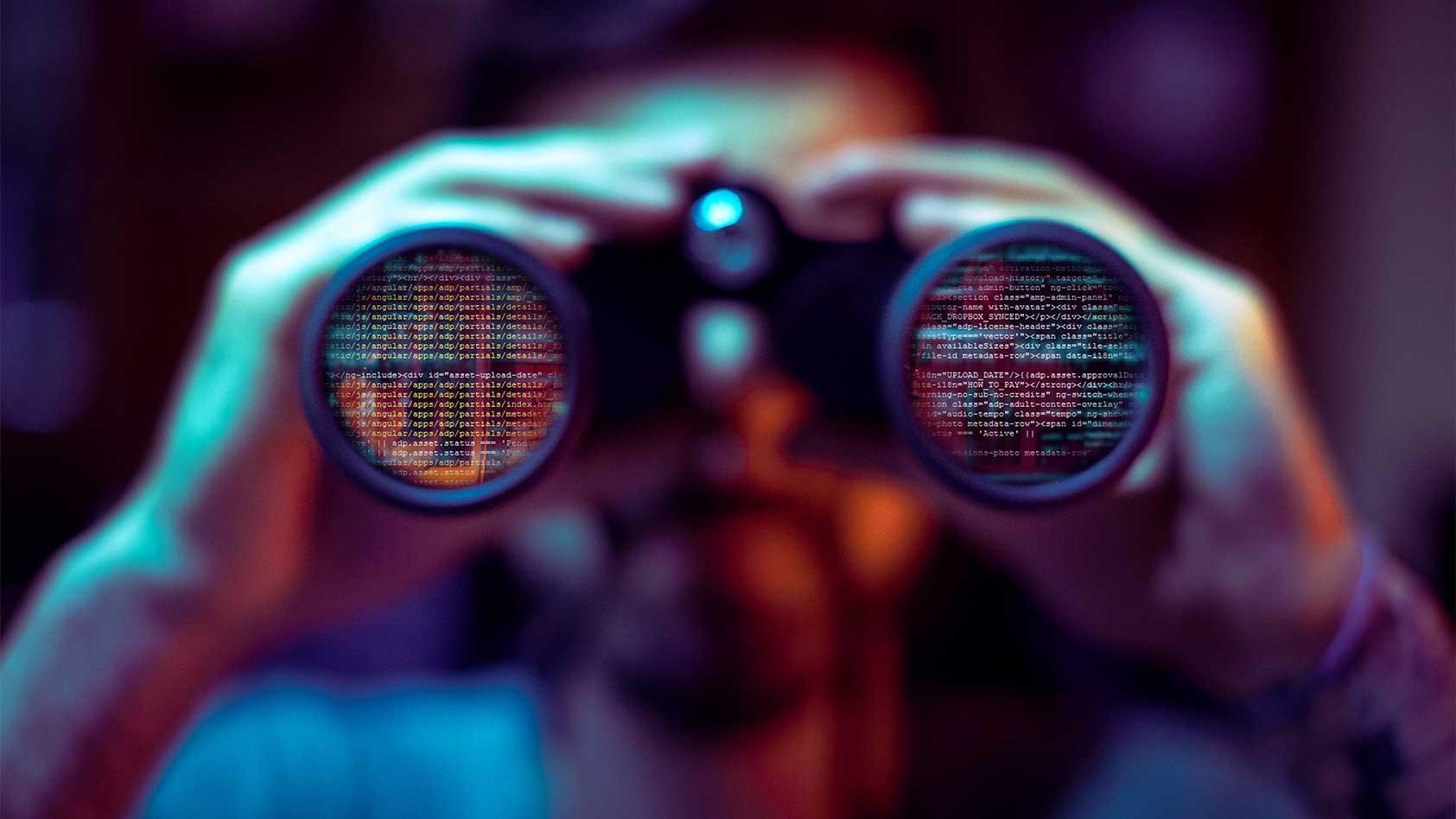 Man looking through binoculars with code superimposed on lenses