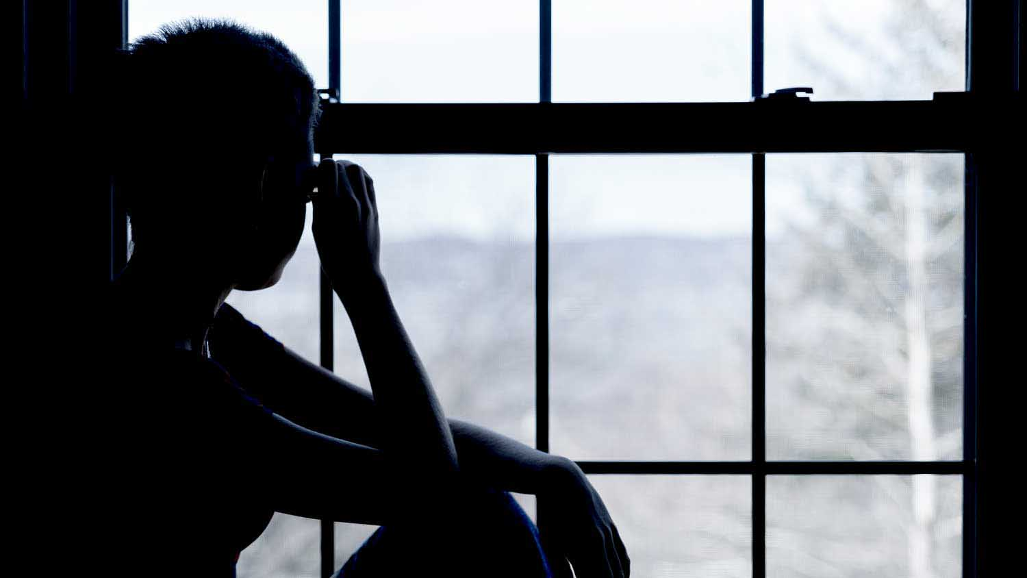 Silhouette of someone looking out of a window