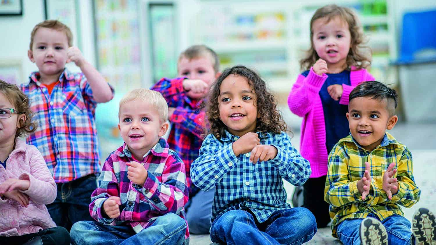 A multi-ethnic group of young children are at a preschool. They are sitting on the carpet and doing various motions to a song.