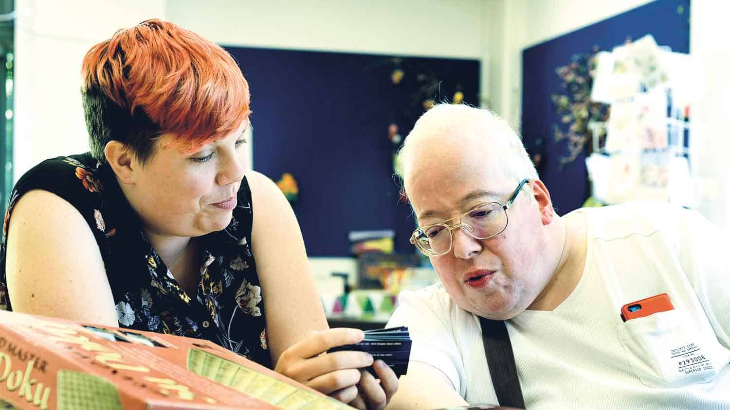 Patient with a carer looking at an electronic display working together