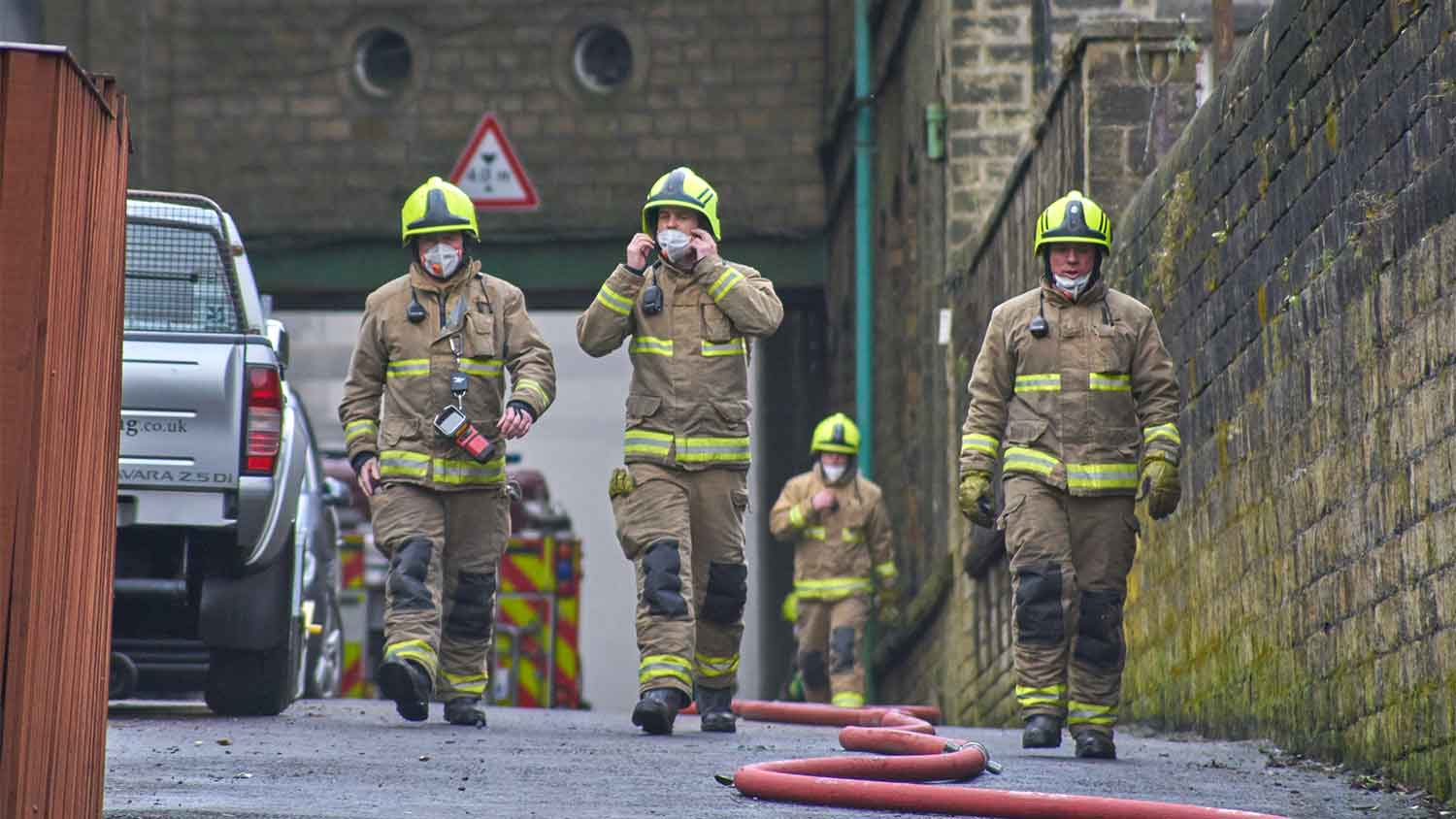 Fire fighters on call, walking with paper masks down a street