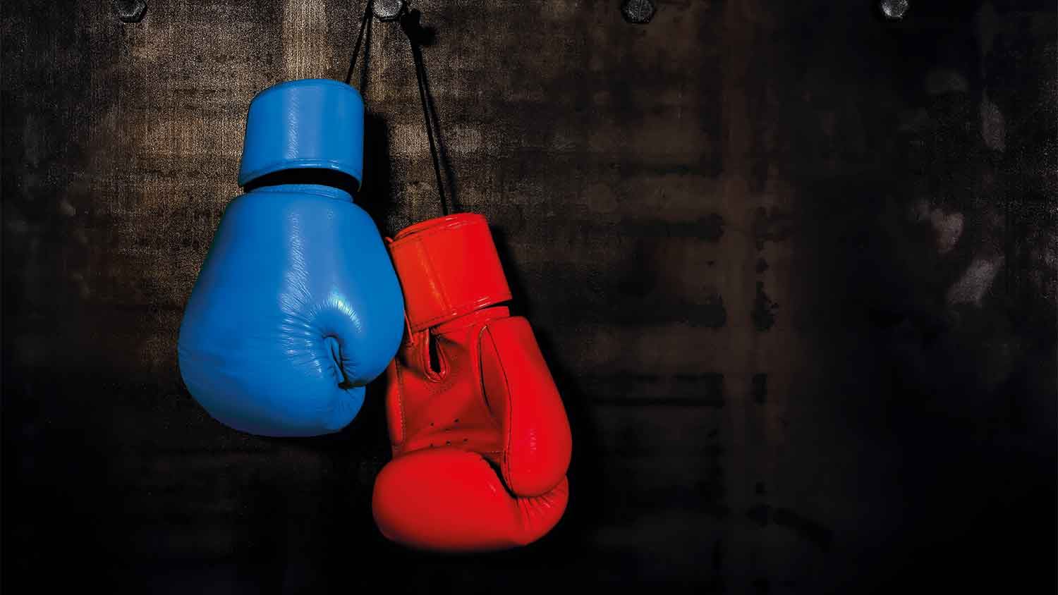 One red boxing glove and one blue boxing glove hanging up