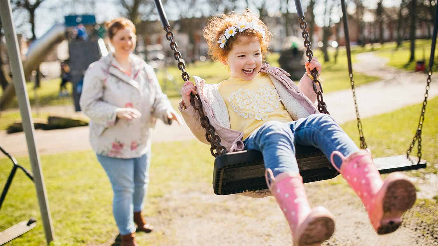 Young girl on a swing in a playground