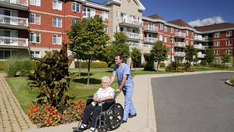 Nurse pushing an older woman in a wheel chair