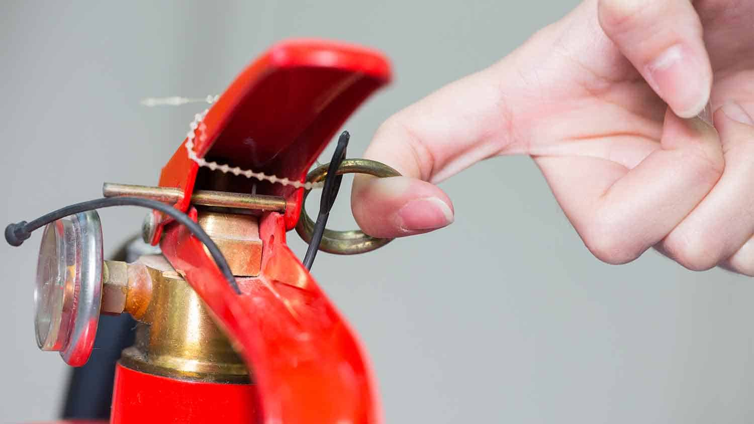 Fire extinguisher pin being pulled