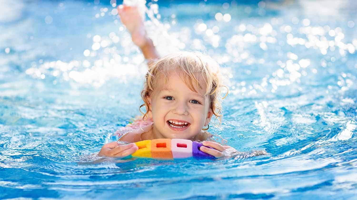 Happy young child swimming