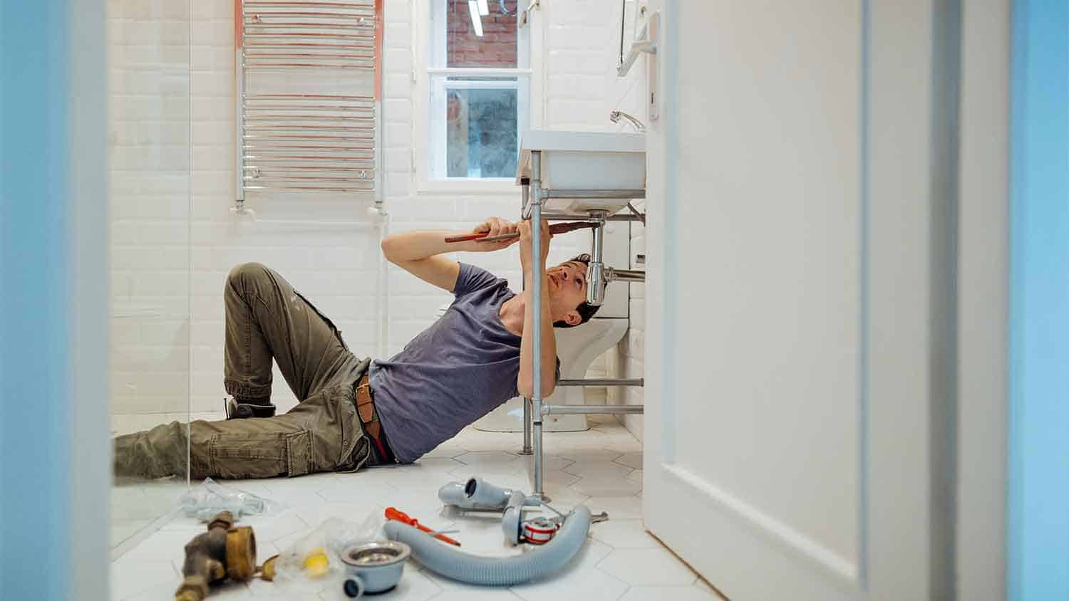 A plumber working under a sink