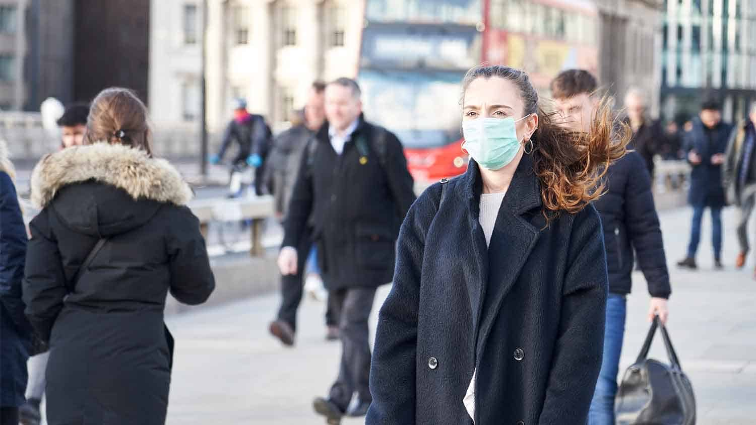 Woman walking and wearing a surgical mask