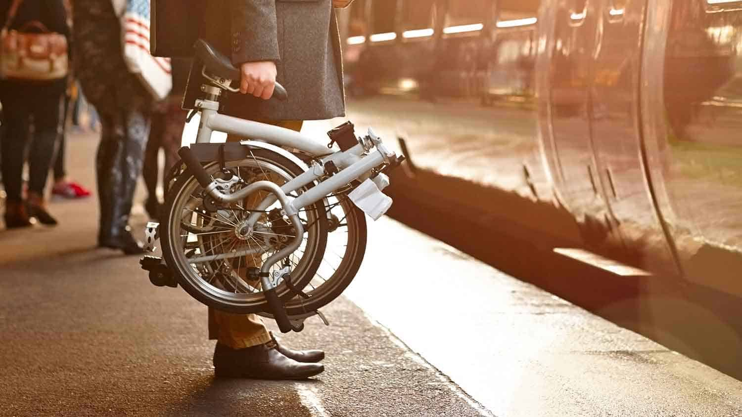 Man with fold up bike getting on a train