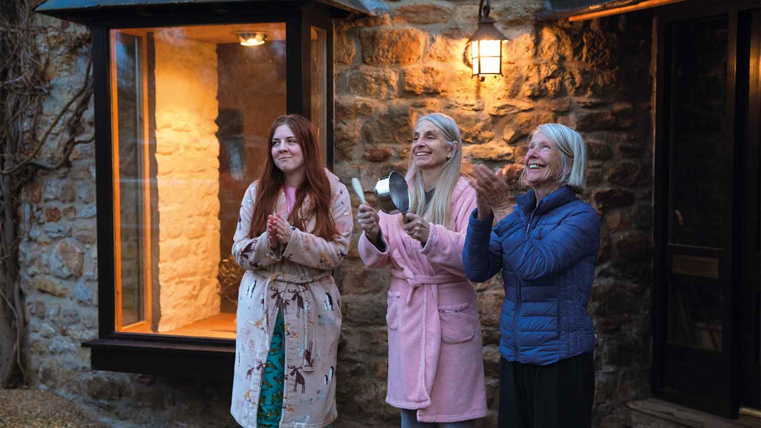 Three women applauding key workers outside their home