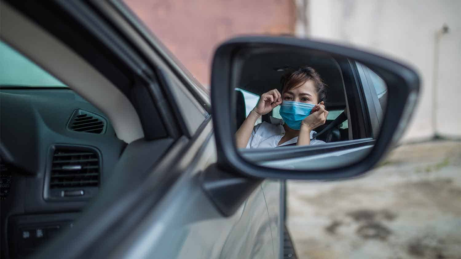 reflection of a woman putting on a face mask in a car wing mirror