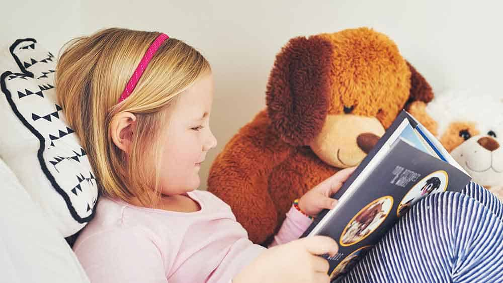 Little girl and a her teddy bear read a book.
