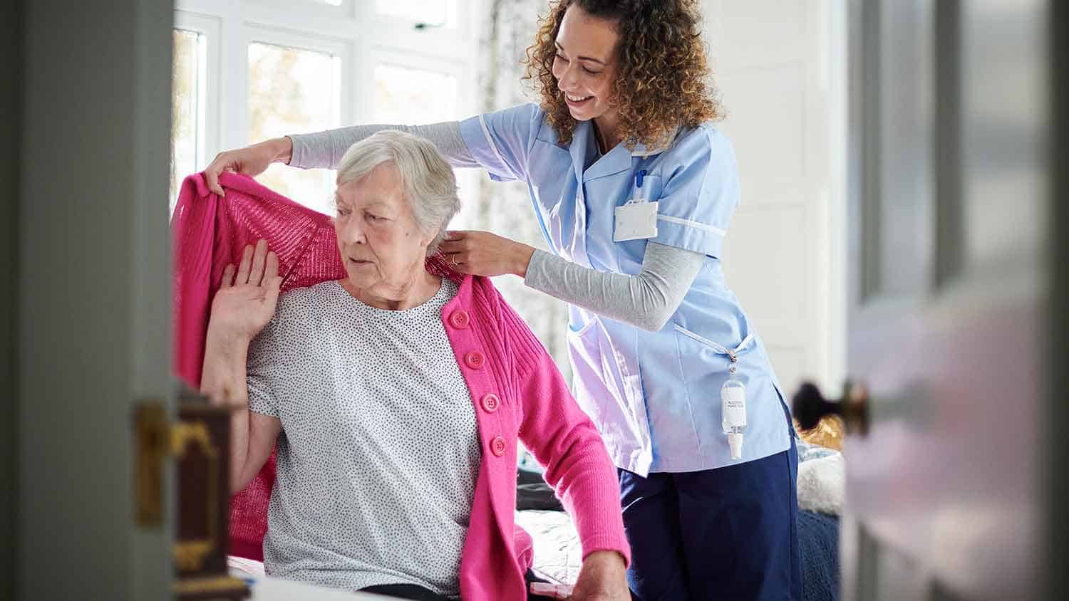 Nurse helping an older lady with a cardigan