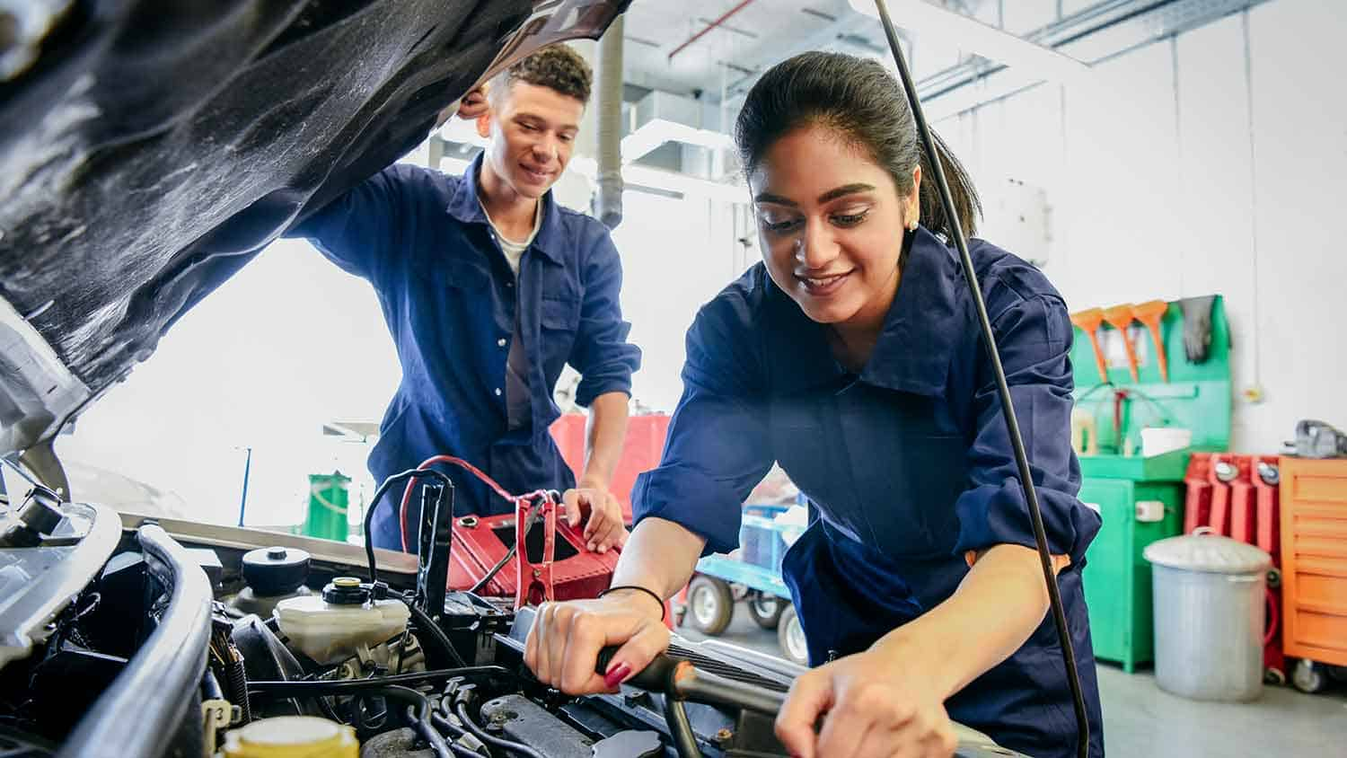 Two young car mechanics working