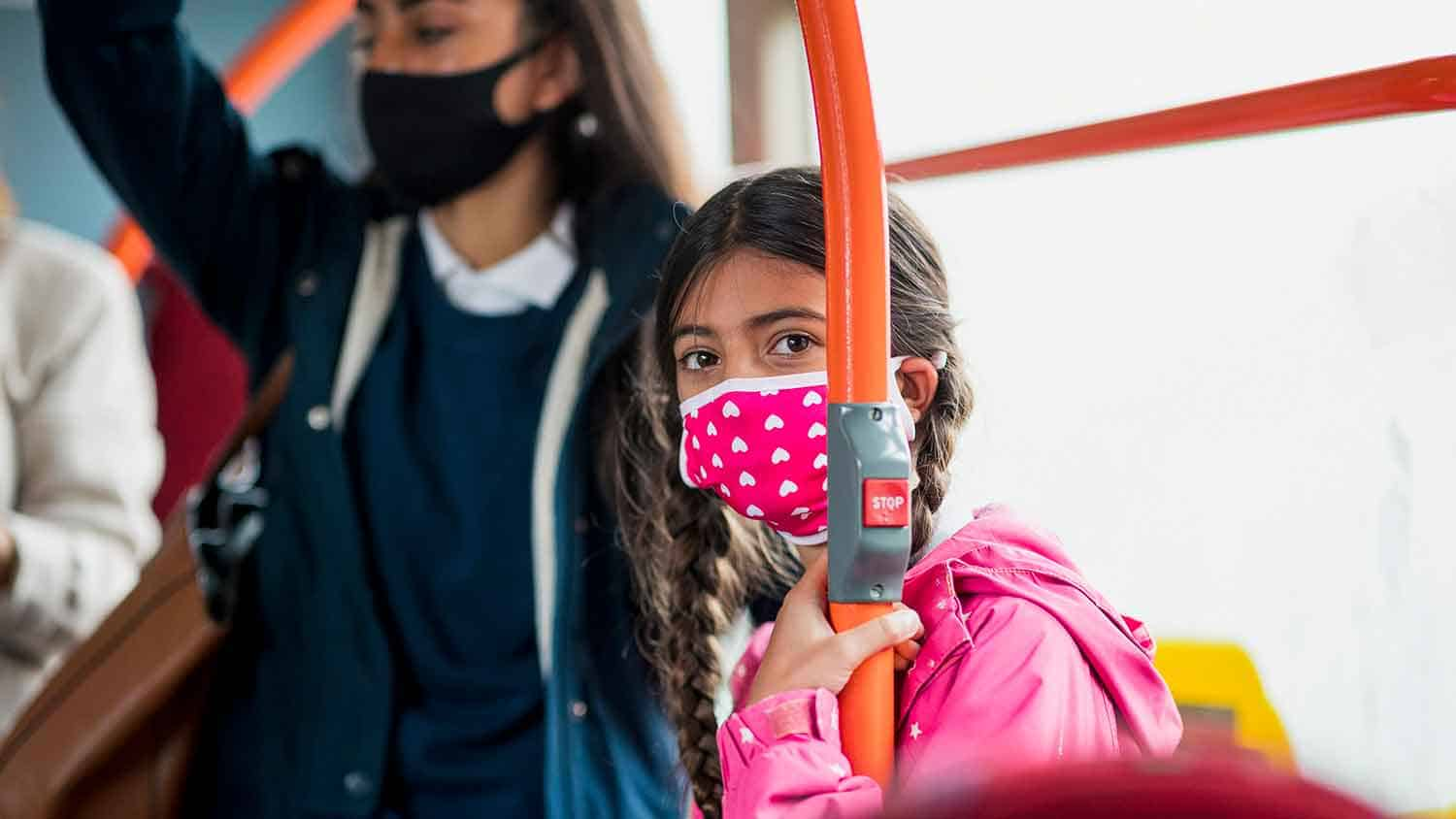 Child in a mask on a bus