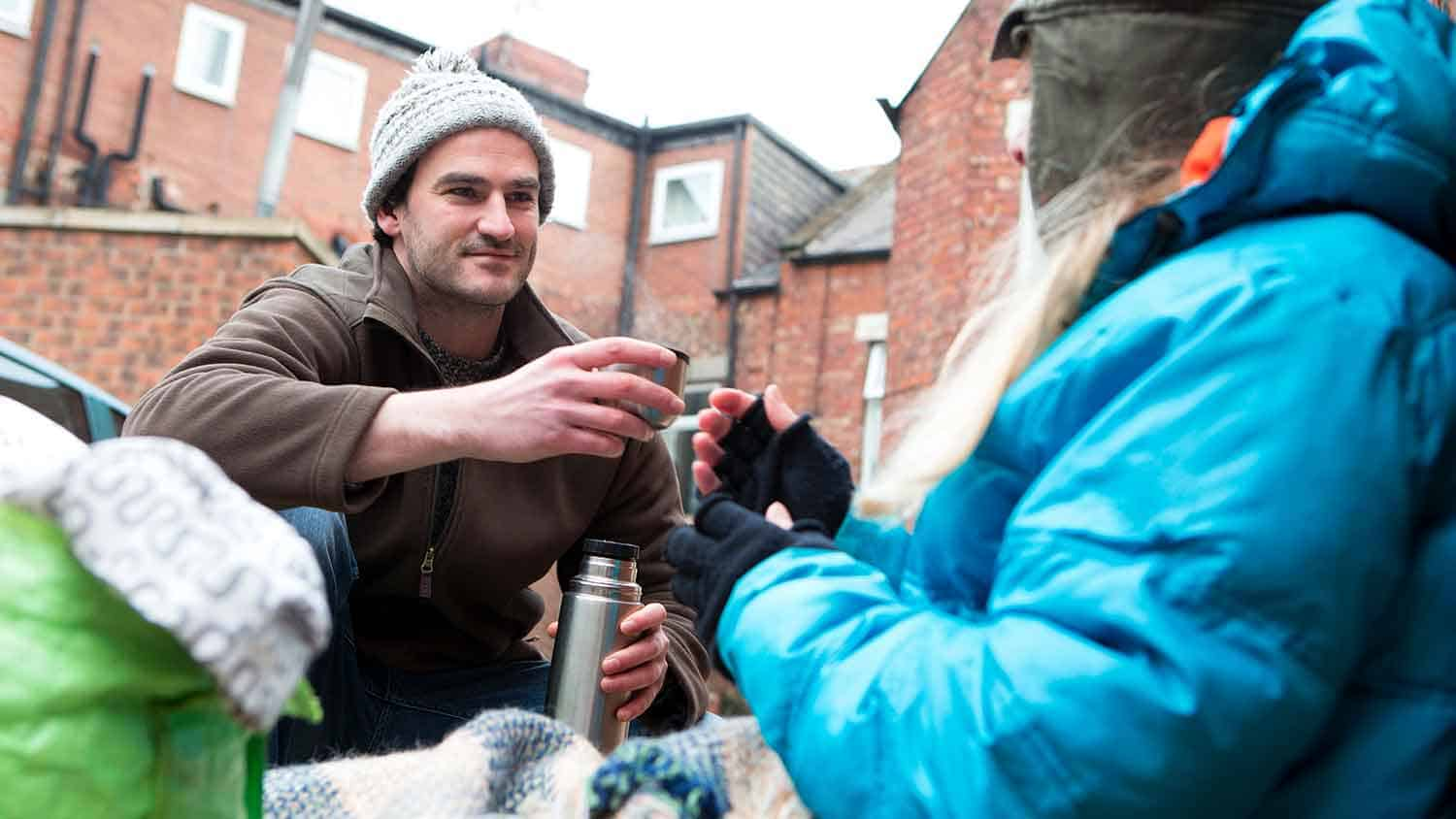 A volunteer sharing a cup of tea with a homeless person