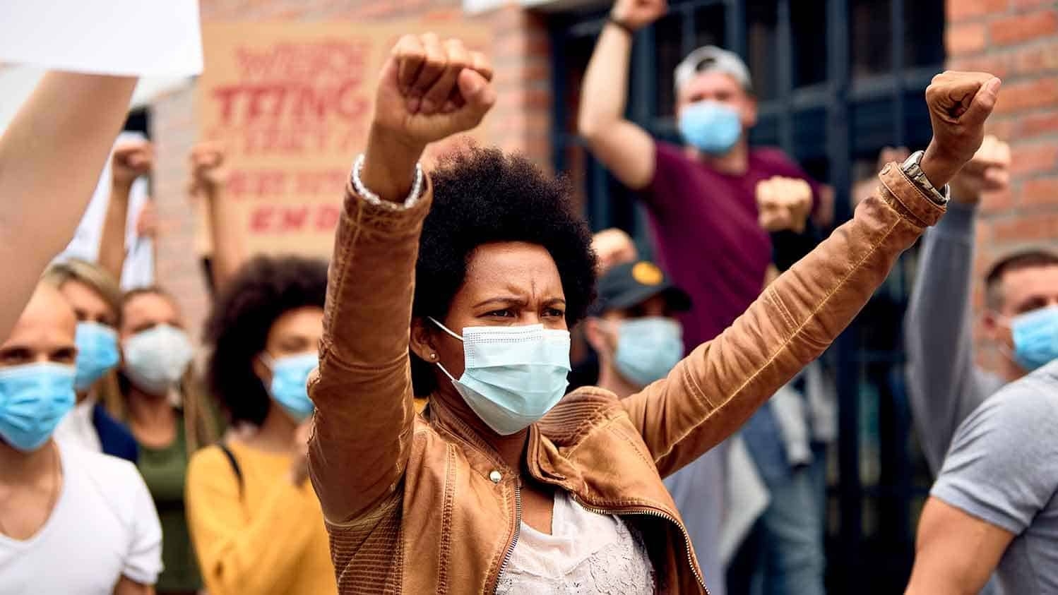 Black woman marching in protest arms aloft, ppe mask on