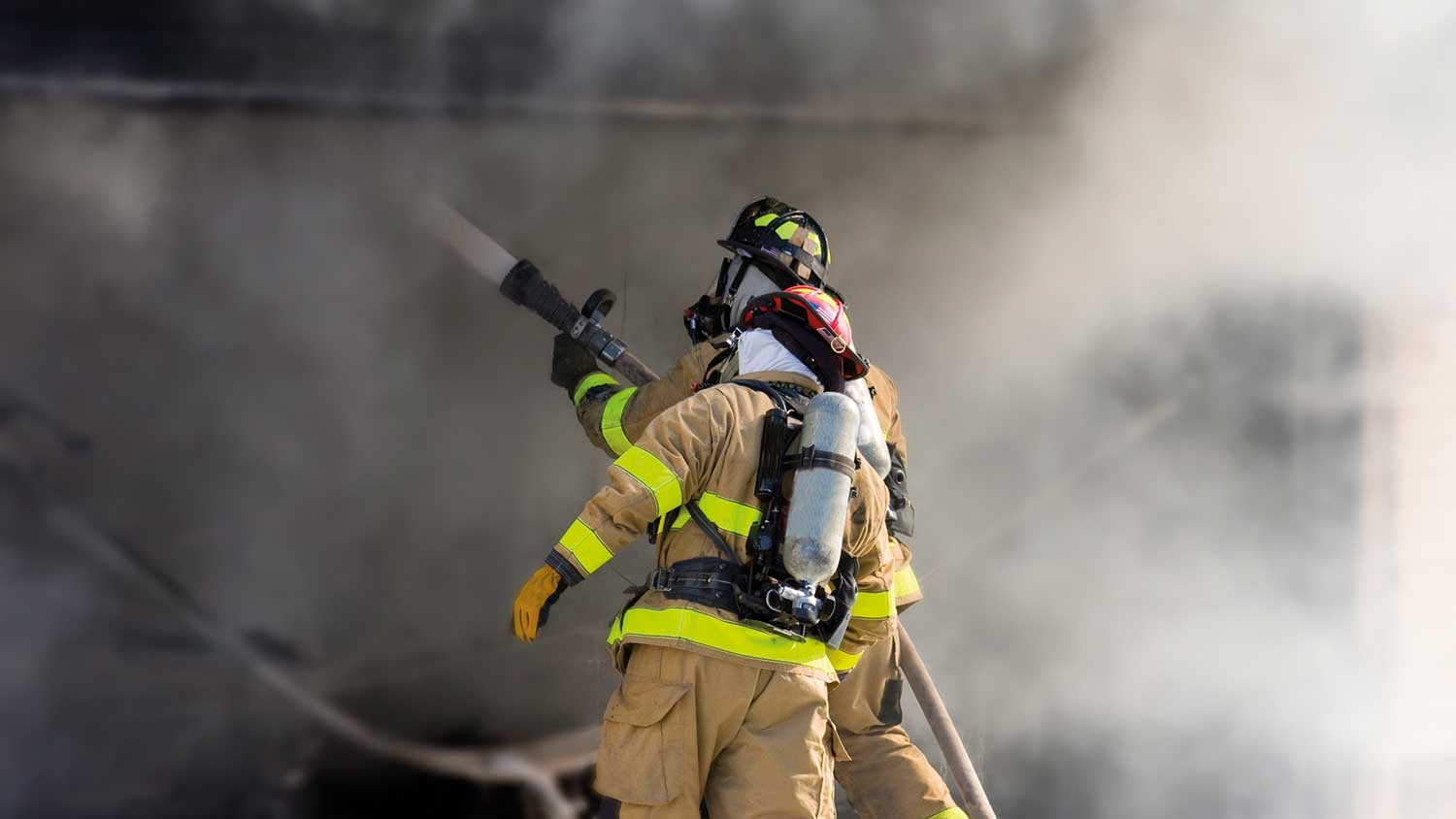 Two firefighters holding the hose and surrounded by smoke