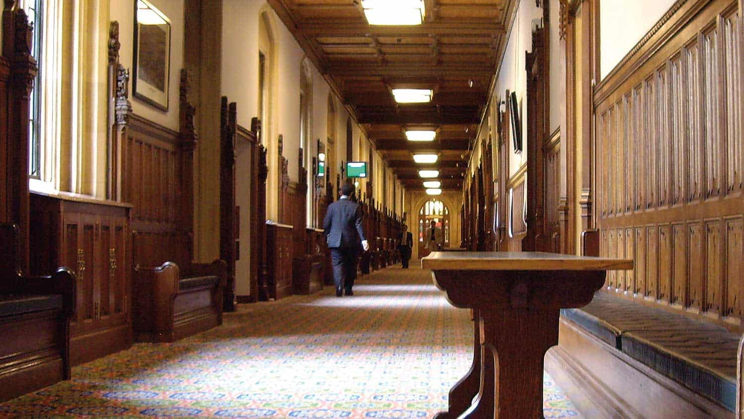 A view down one of parliament's long corridors, empty aside from a bench