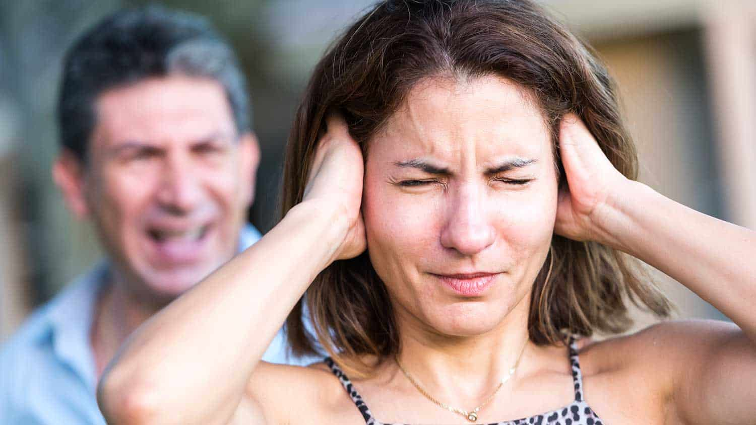 Man shouting at a woman who has her hands over her ears wincing with pain