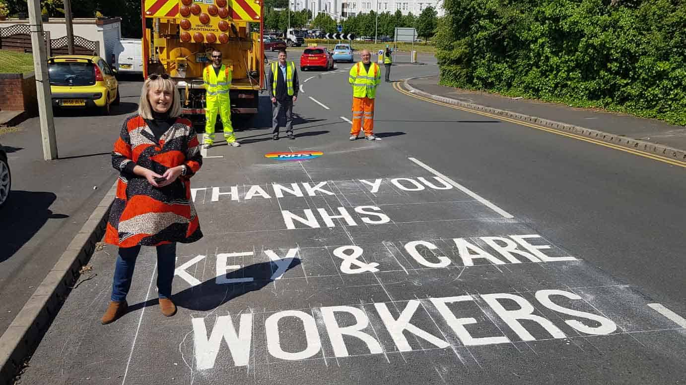 Highways team next to a 'thank you key workers' sign on the road written in chalk
