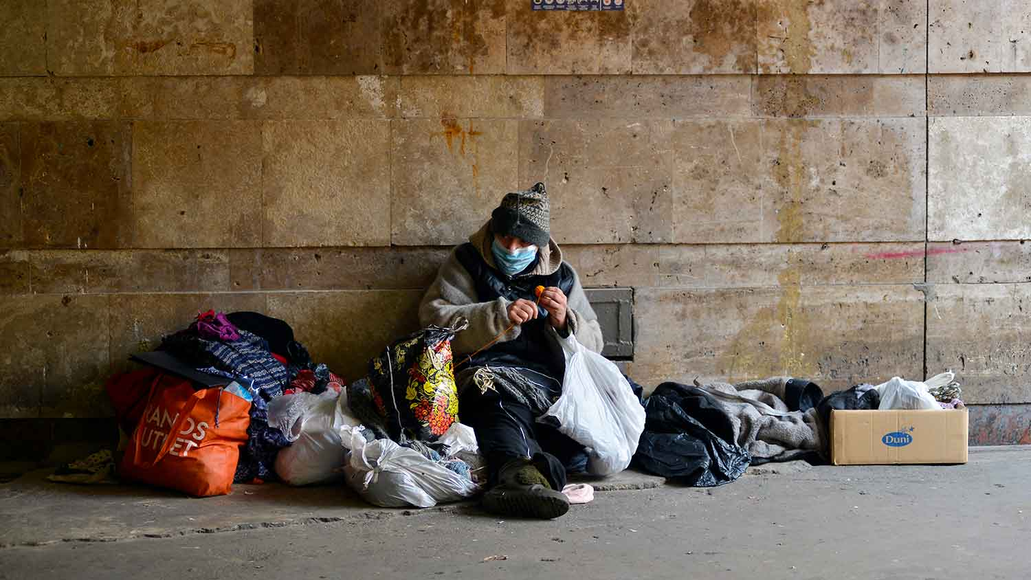 A homeless person sitting on a street surrounded by belongings