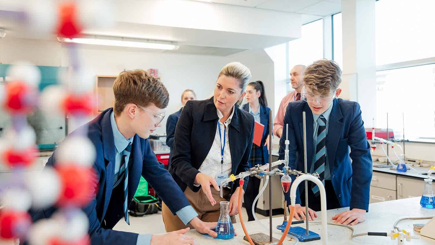 Two students in a science lesson being taught by a teacher