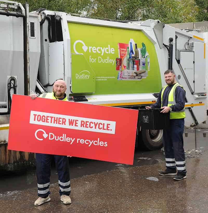 Recyling pick up truck with two workers holding a 'together we recycle' sign