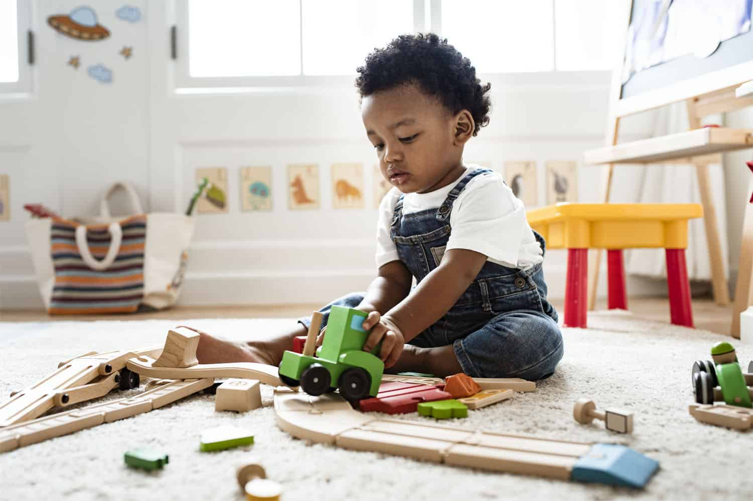 Child playing with a toy train set