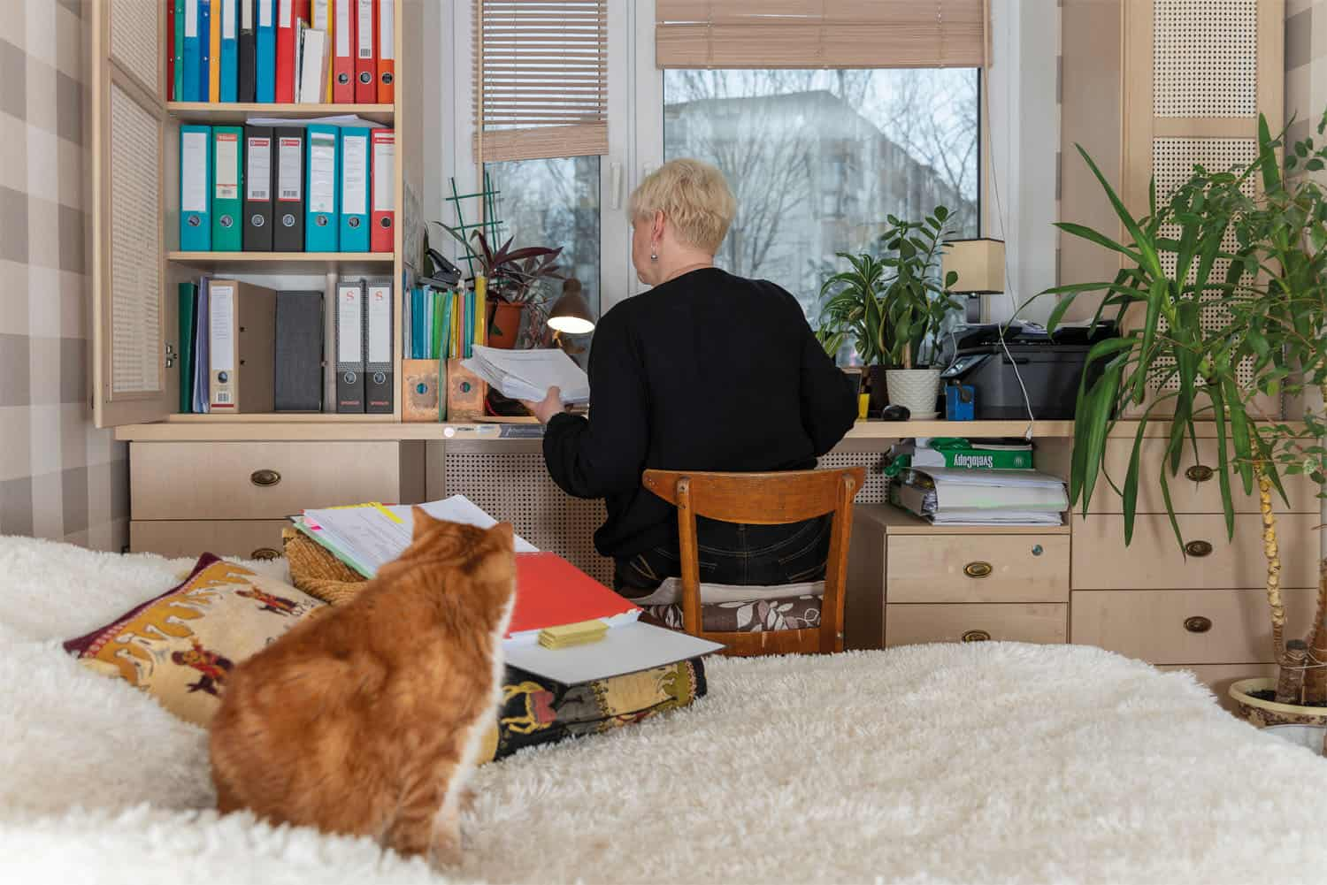 A lady studying at her computer in her bedroom