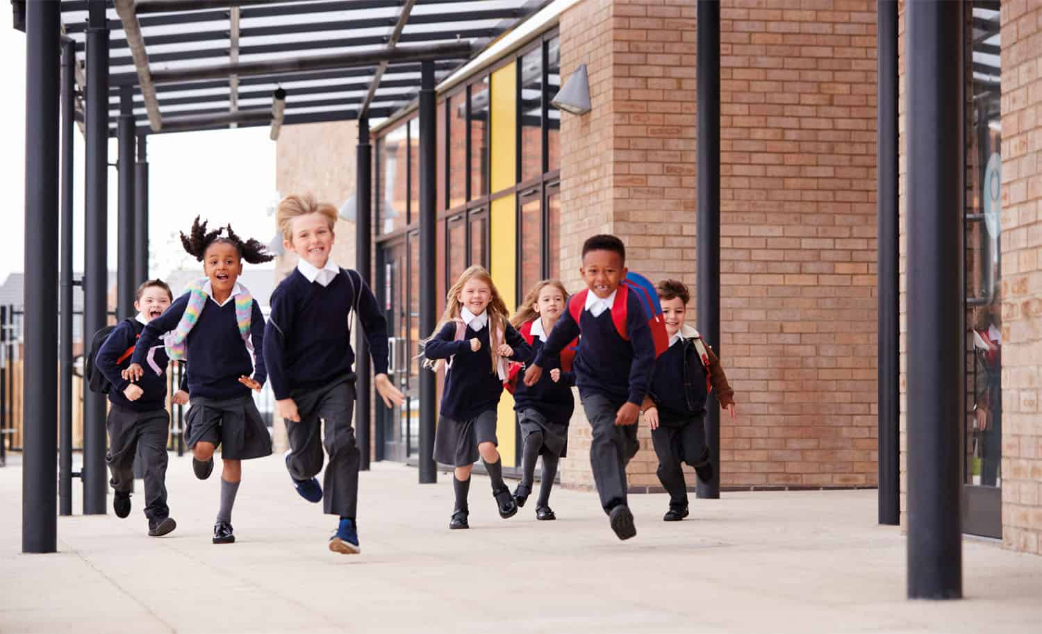 A group of school children running excitedly out of the building