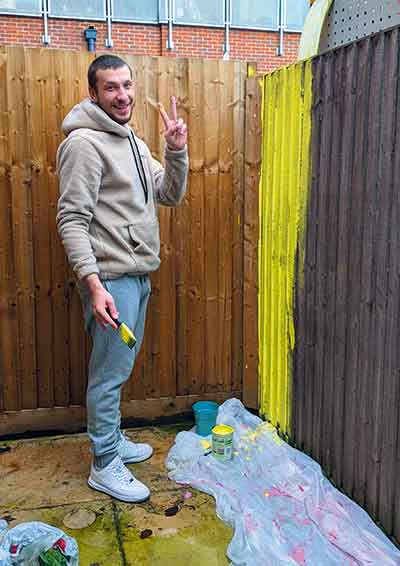 Man smiling at the camera doing a peace sign after painting a fence bright yellow