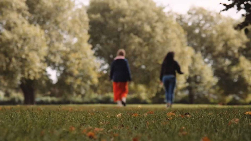 Two women walking in a leafy park away from the camera, they are slightly out of focus