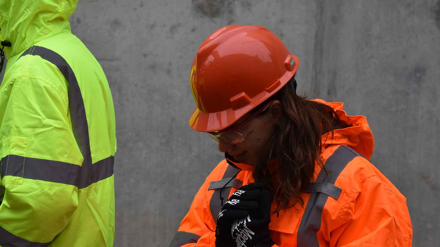 A construction worker with a red hard hat and orange hi-vis