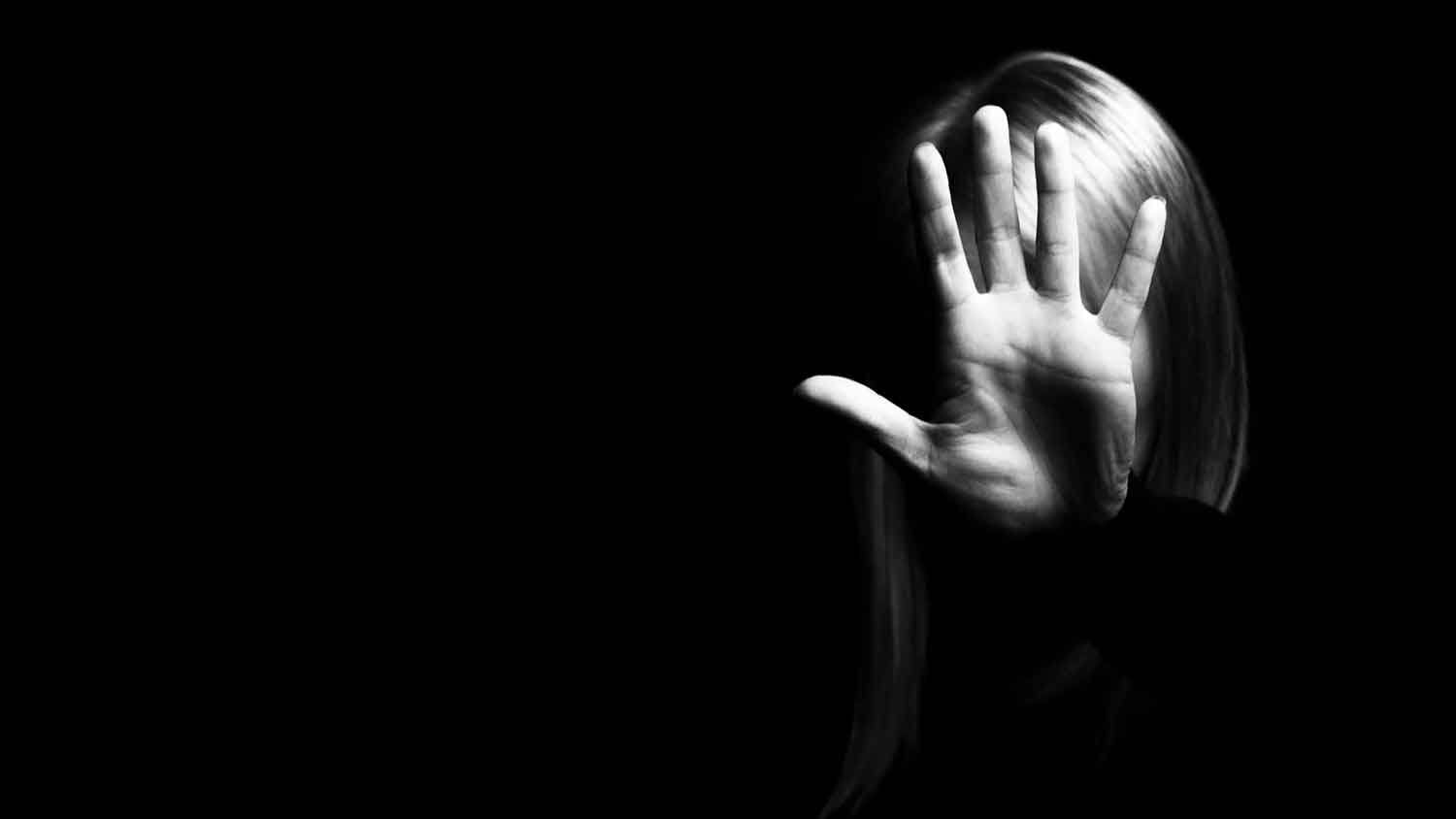 Black and white image of a woman holding her hand toward the camera to obscure her face
