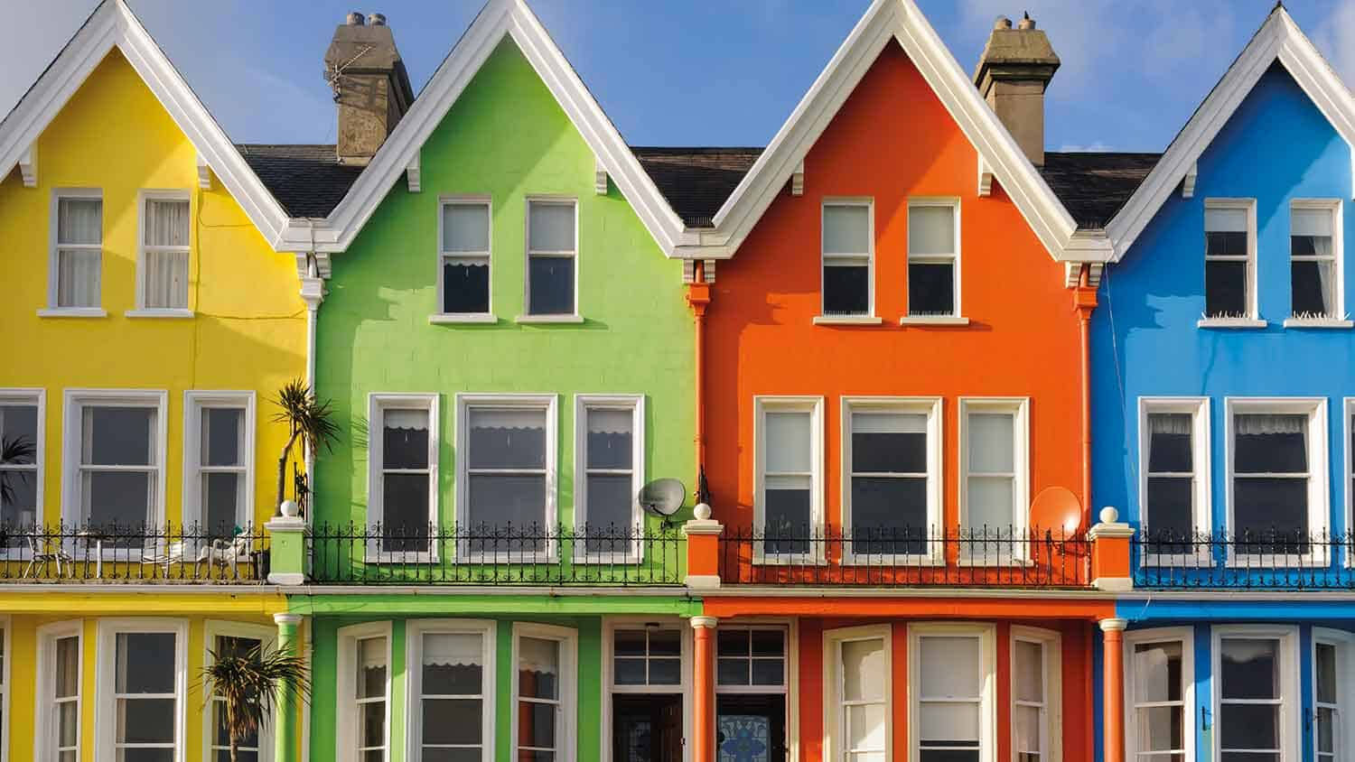 Row of houses painted in bright colours. From left to right they are yellow, green, orange and blue. All against a sunny blue sky