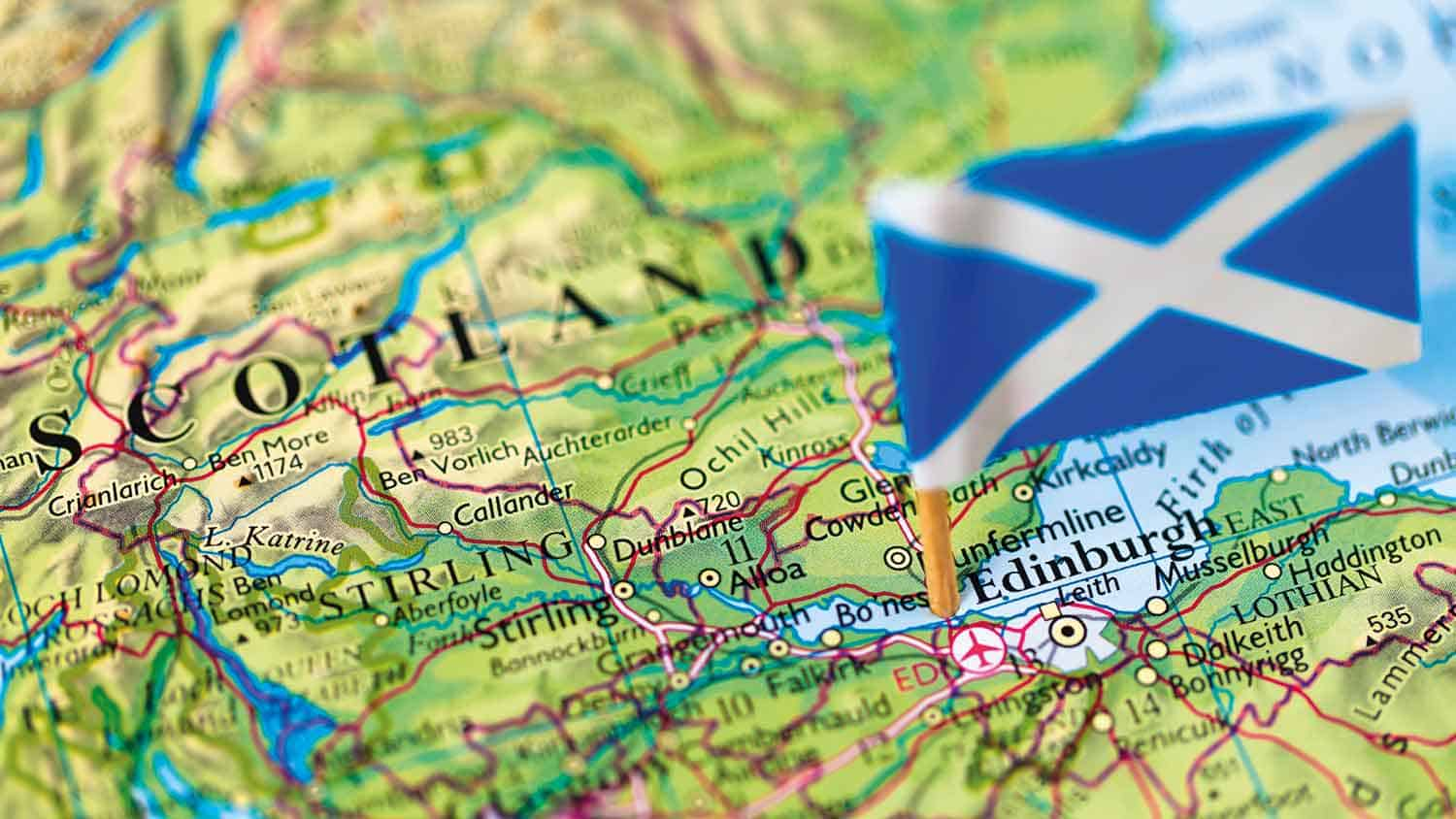 Scotland flag on a small wooden stick poked into Edinburgh on a map of Scotland