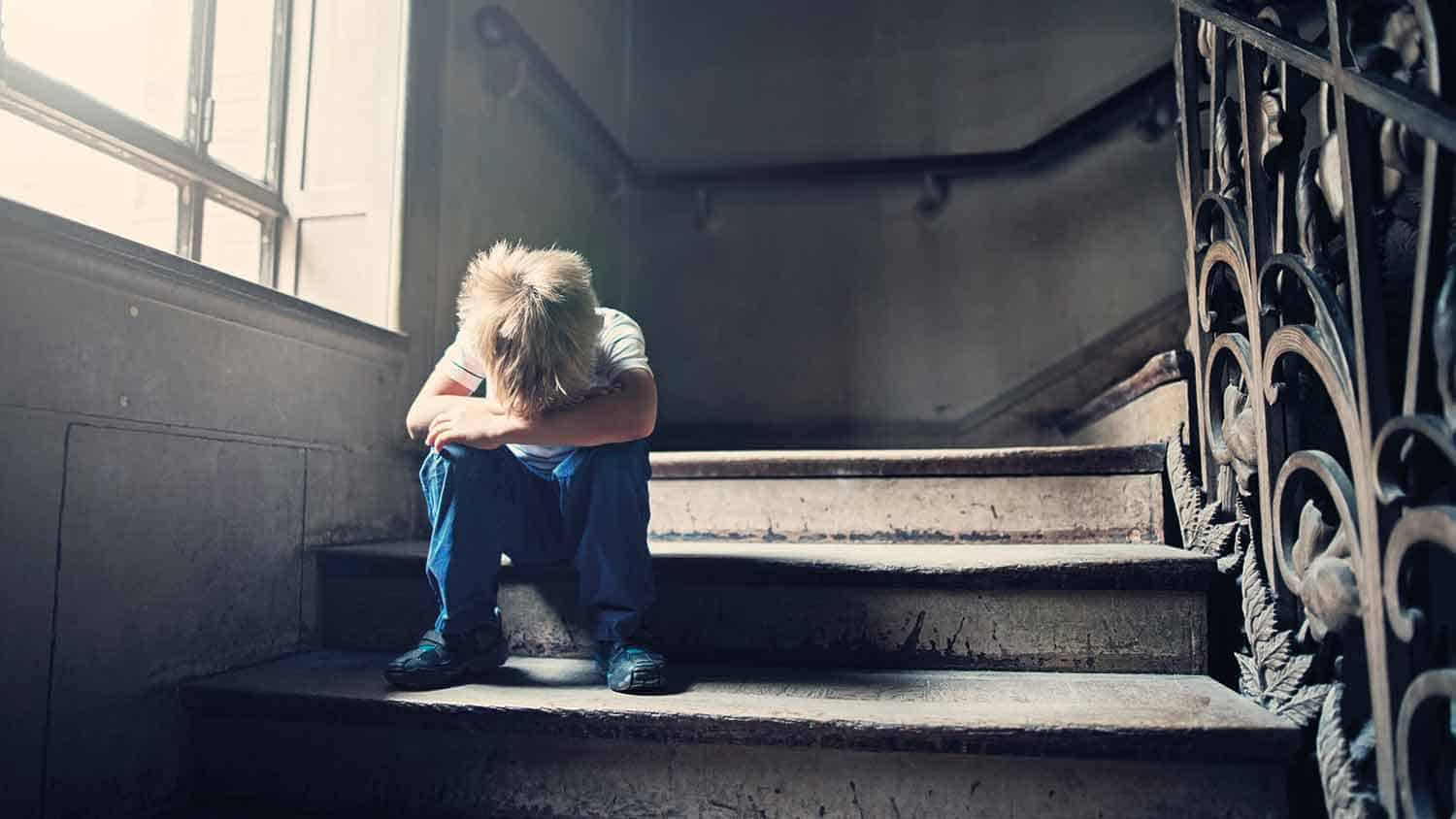 Small boy crying on the stairs, head in hands