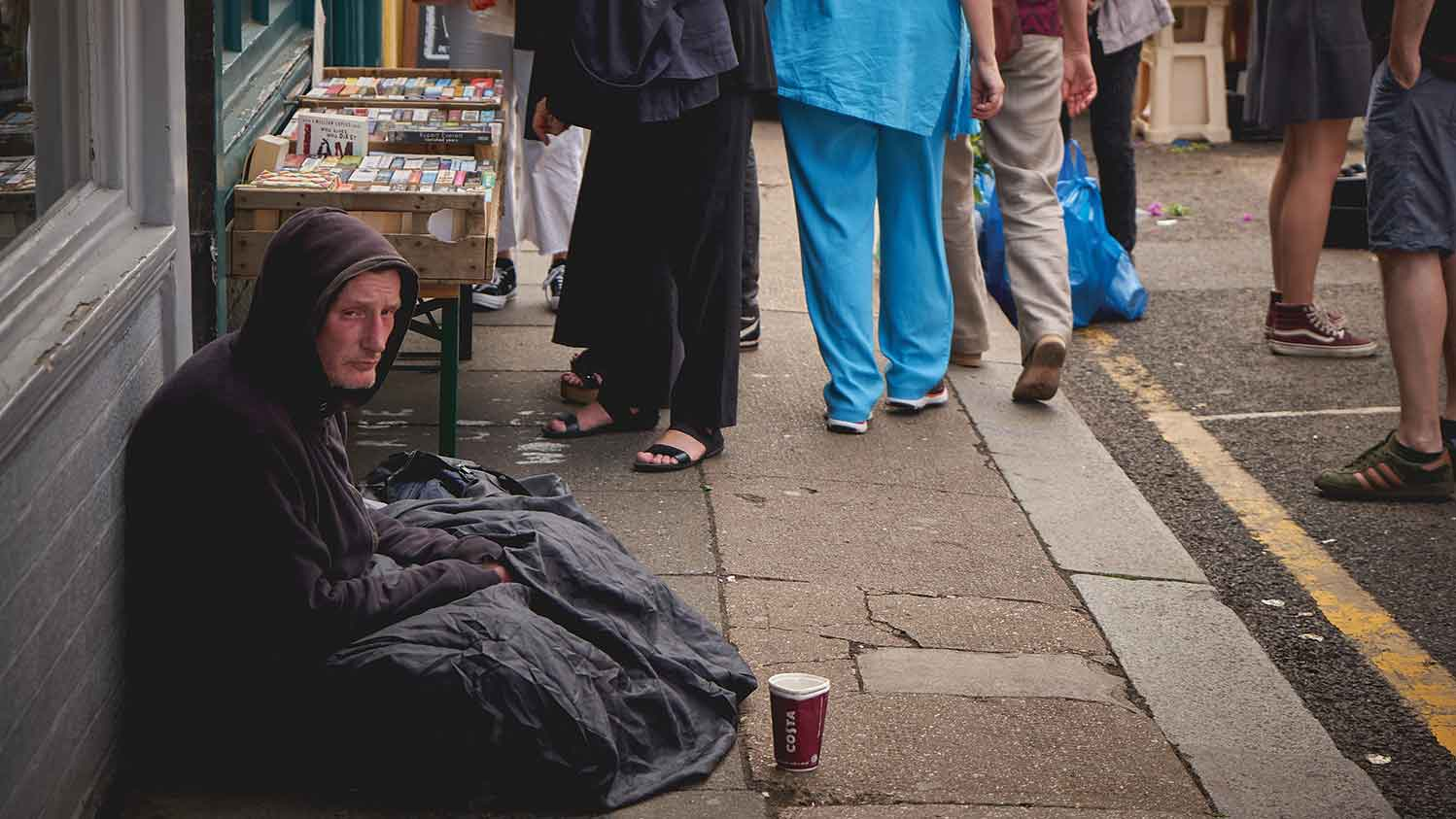 Homeless man sat on the pavement with a coffee cup for money in front of him